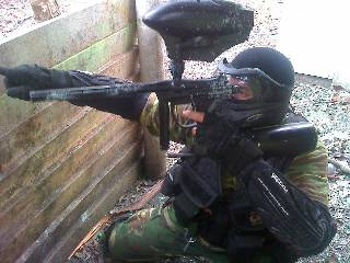 Signaling to his fellow paintball players where the enemy is. That and making a cool pose.